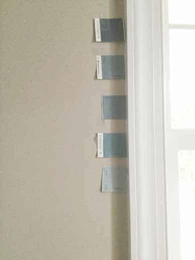 five blue paint chips in vertical line taped wall next to window