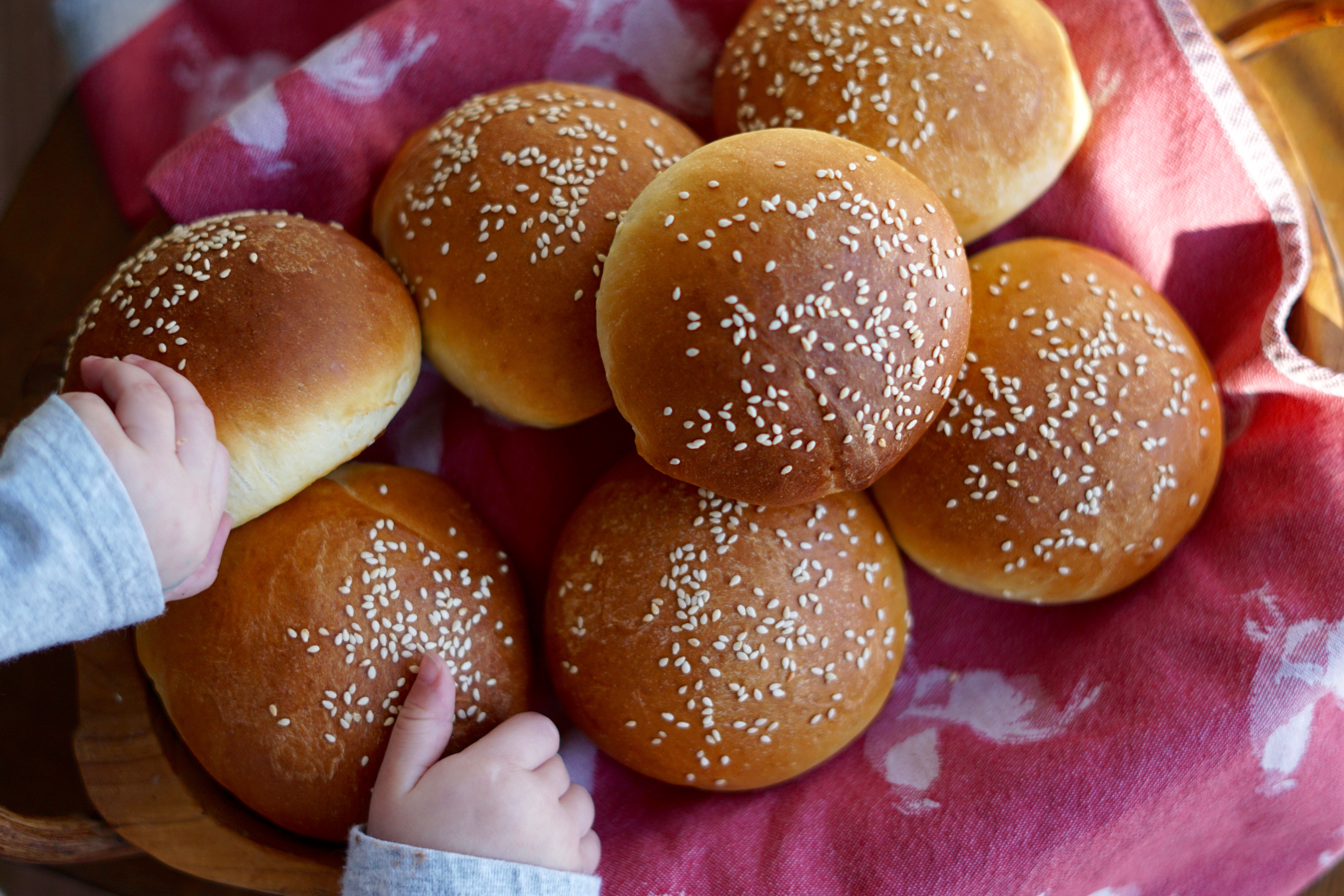 brioche buns with sesame seeds on top of red tea towel in wooden bowl.  small hand reaching in to grab one.