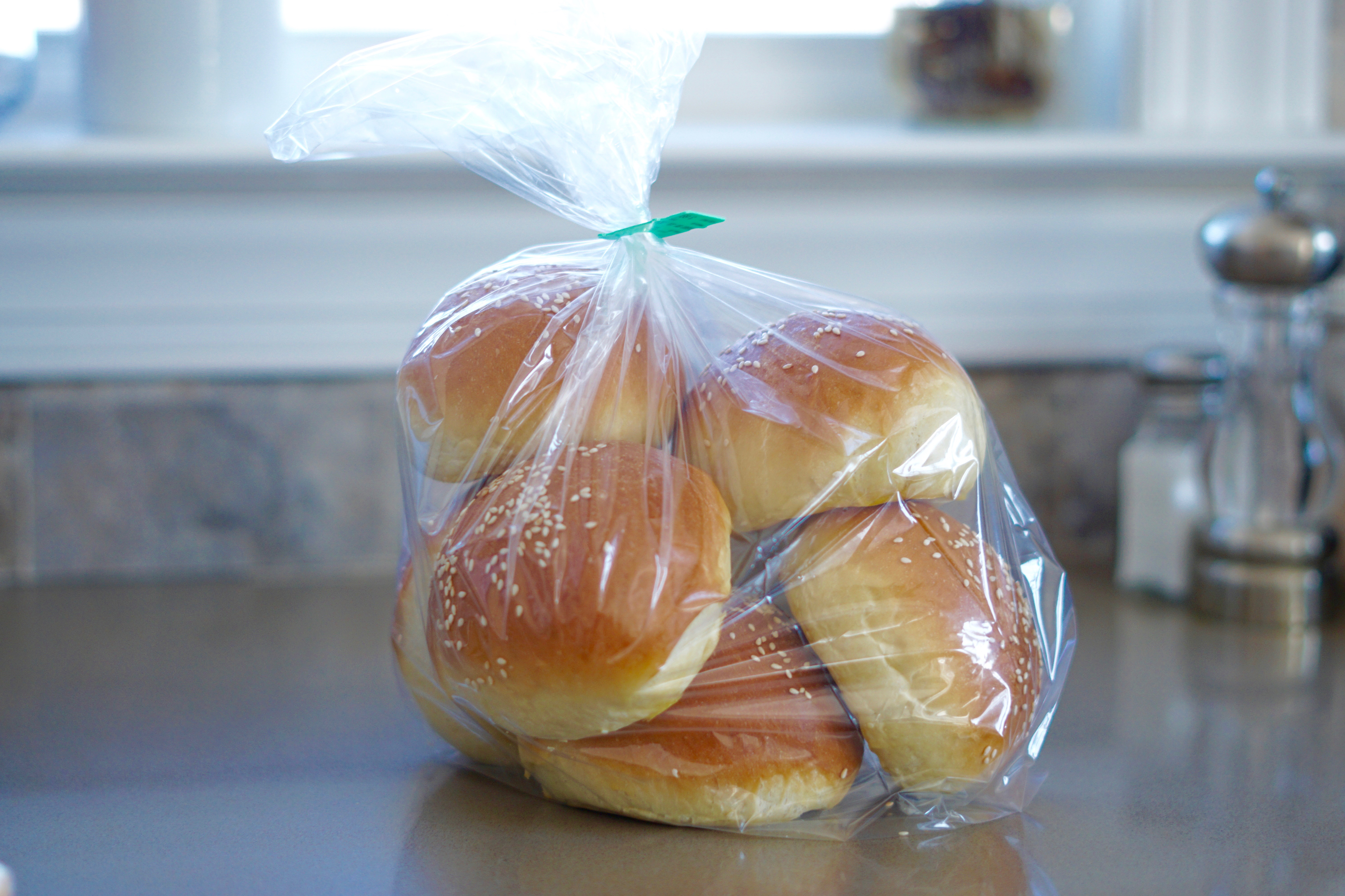 brioche style buns inside a plastic bag resting on a countertop