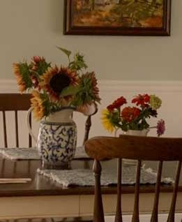 two bouquets on dining room table: one with plum procut sunflowers, one with red and green zinnias