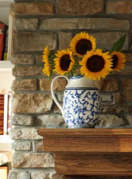 pro cut orange sunflowers on fireplace