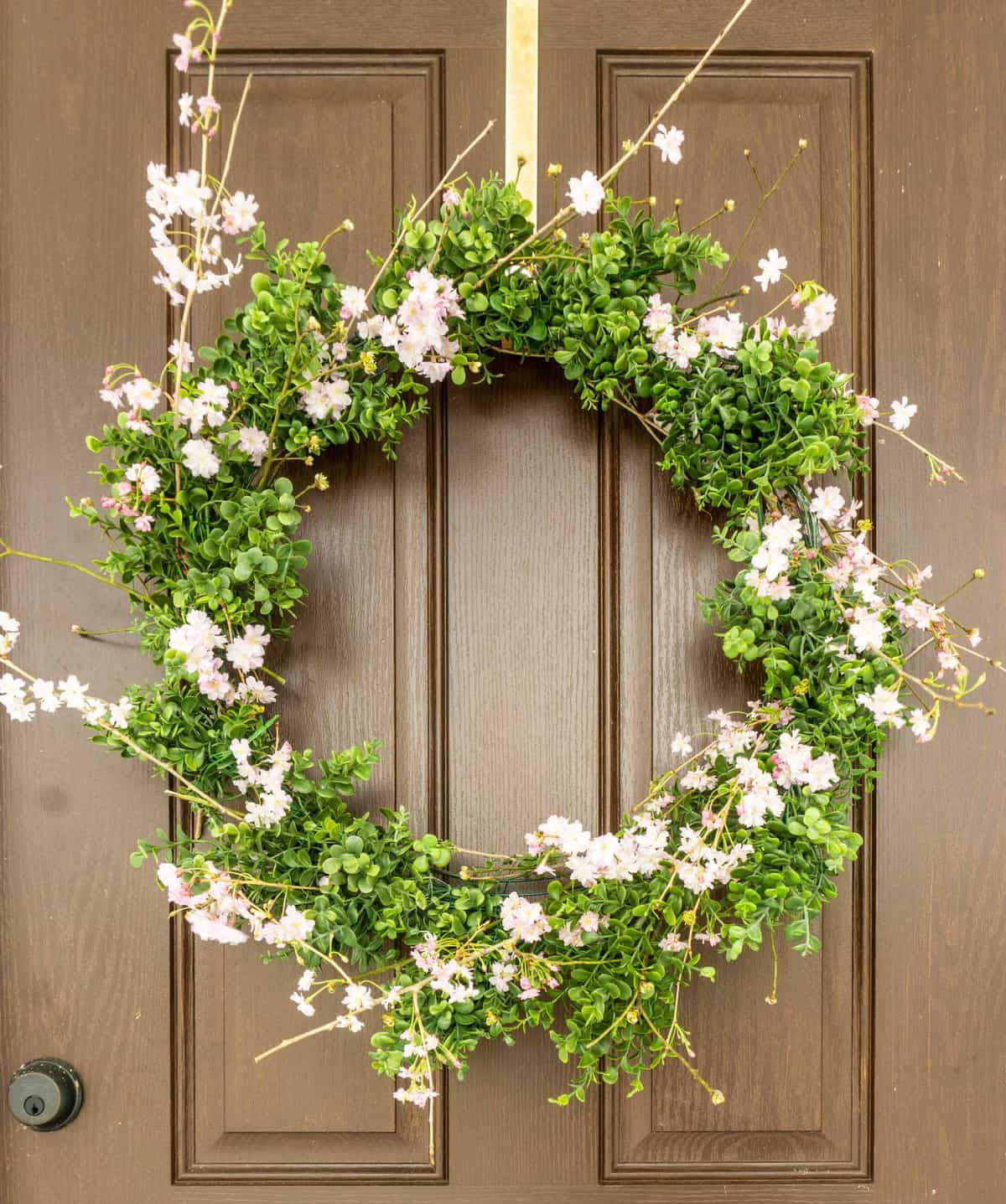 wreath on door with artificial boxwood and natural flowers