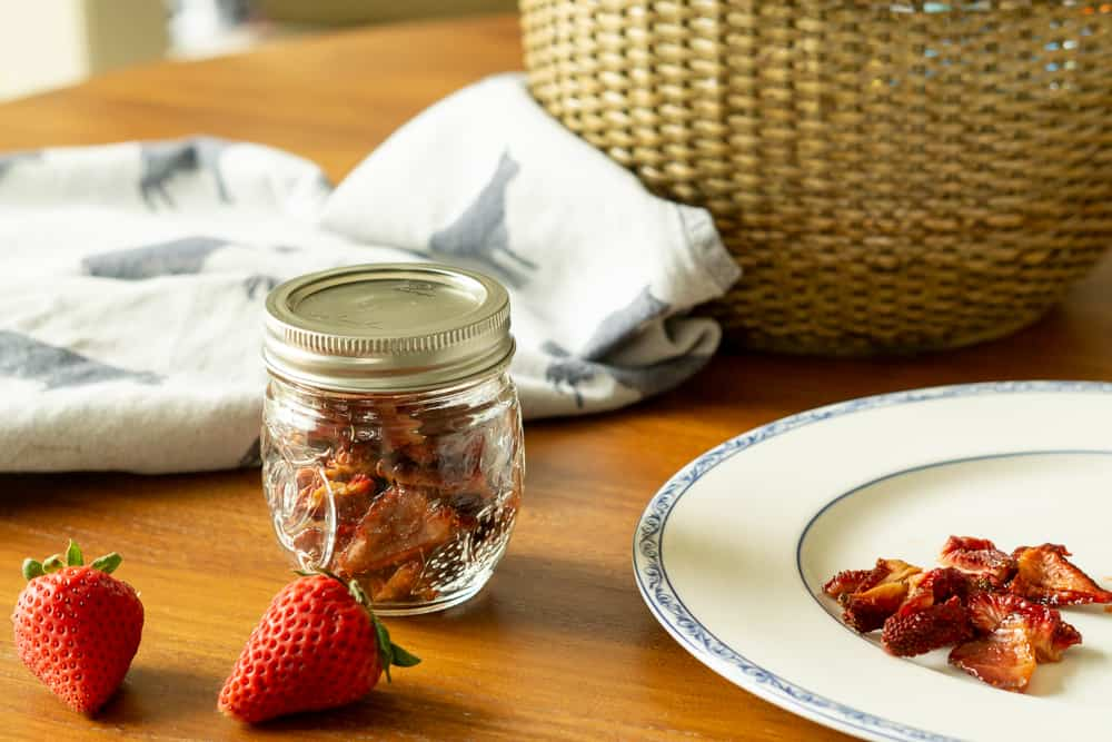 dried strawberries in mason jar, with some on plate, basket in background