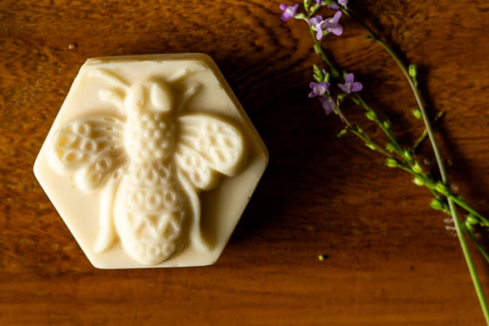 bar of honey and beeswax soap next to flower