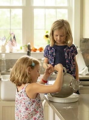 two little girls around kitchen island, baking