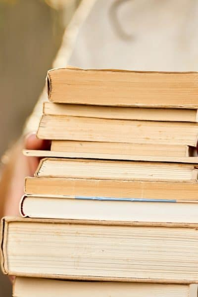 stack of 7 books in woman hand