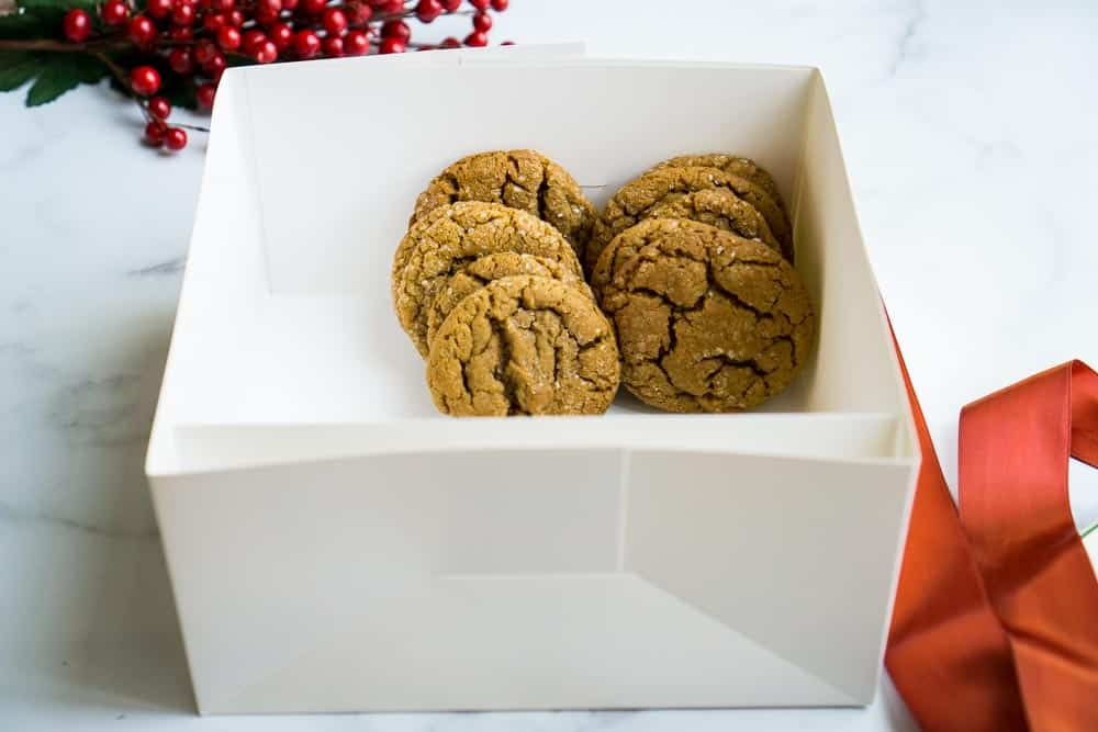 molasses cookies lined up in gift box with berries in background