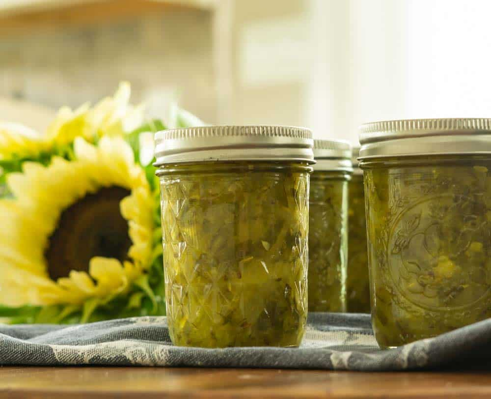 mason jars filled with relish next to sunflowers