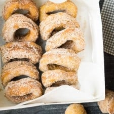 a dozen apple cider doughnuts in white box lined up