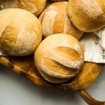 four wheat dinner rolls in bowl, slashed tops and dusted with white flour