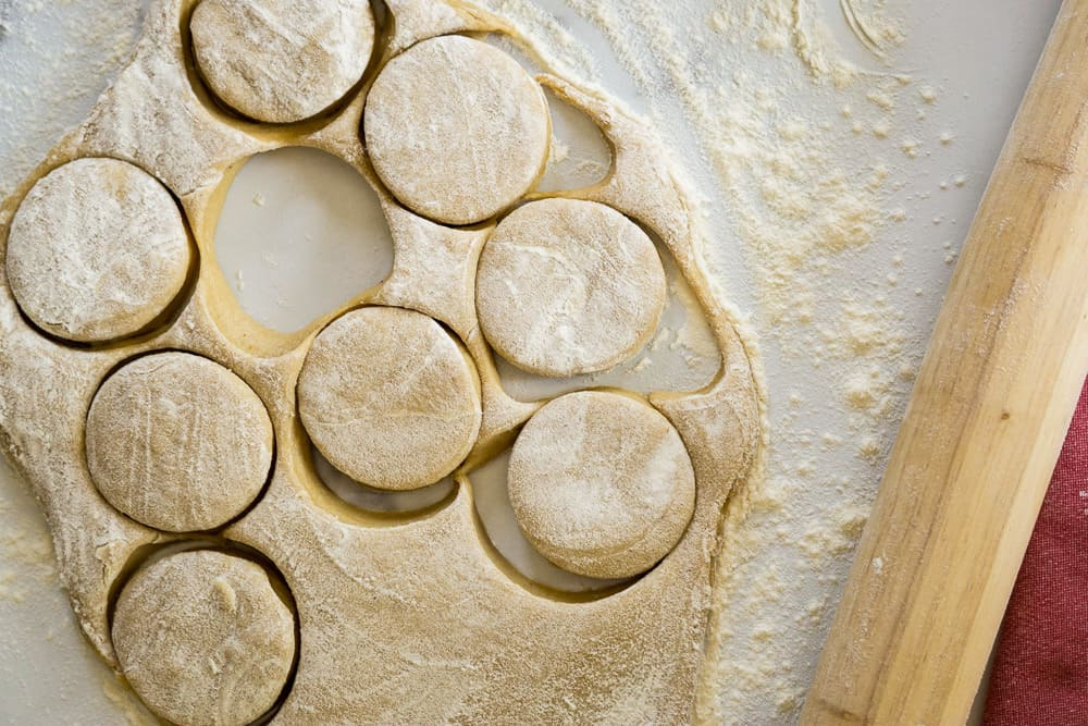 dough for apple cider donut rolled in oval cut out circles and wooden rolling pin nearby
