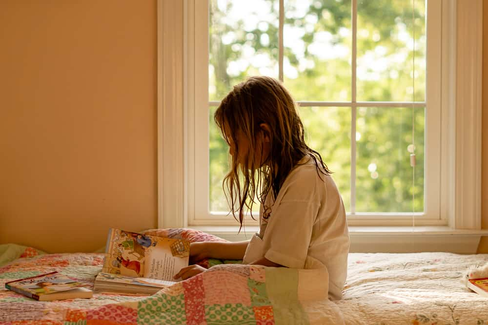 young girl reading in front of window, sitting on bed in front of Queen Anne pink wall