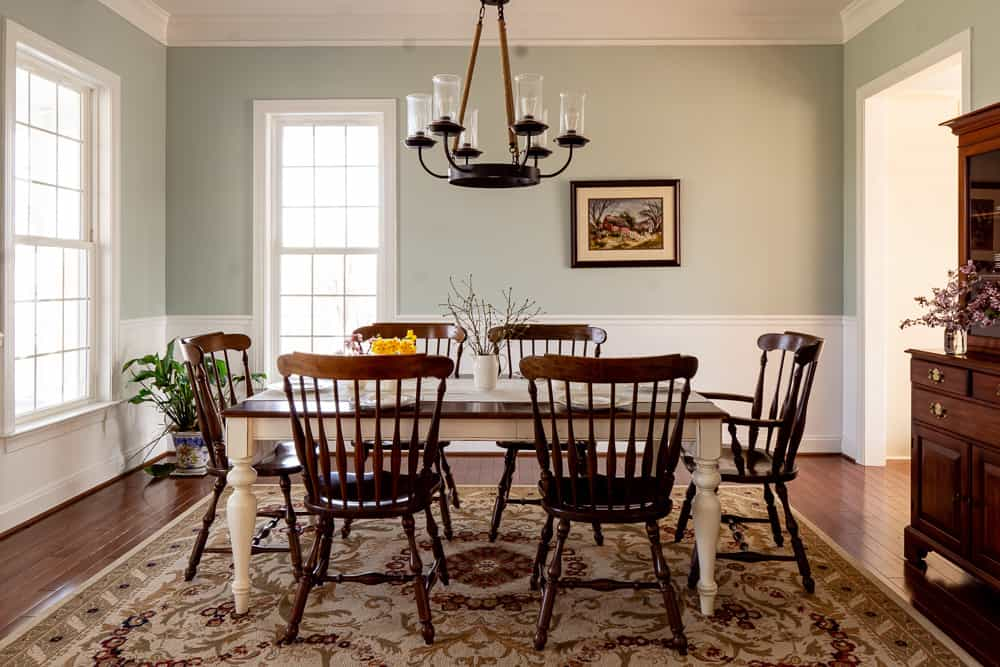 dining room with long table, dark wooden chairs, and gray blue walls