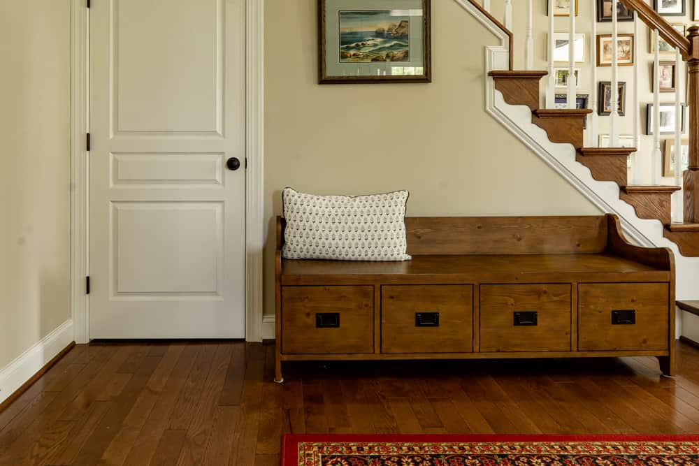 wooden bench in front of stairs, wall behind painted warm gray