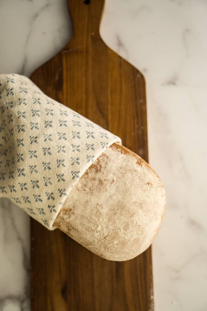 load of sandwich bread wrapped in blue and white tea towel laid on wooden cutting board