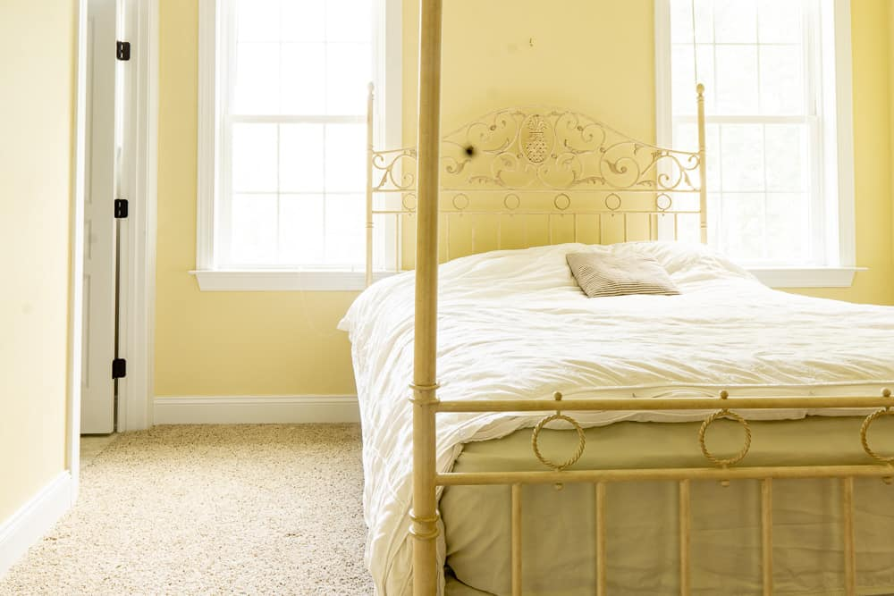 view of bedroom with bed facing doorway.  bed set between two windows, walls are golden yellow, painted Benjamin Moore Philadelphia cream