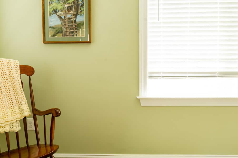 Wooden rocking chair in front of window with grayish green walls (Guilford Green)