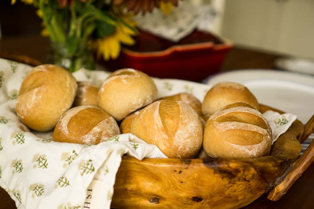 12 honey wheat rolls in wooden bowl with floral tea towel underneath