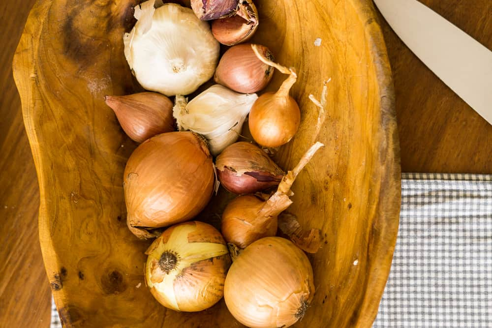 onions and garlic in shallow wooden bowl with large knife and checkered napkin nearby