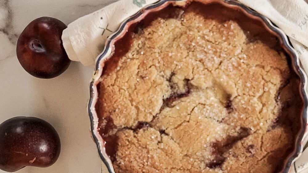 baked plum cobbler with tea towel on side and fresh plum on counter