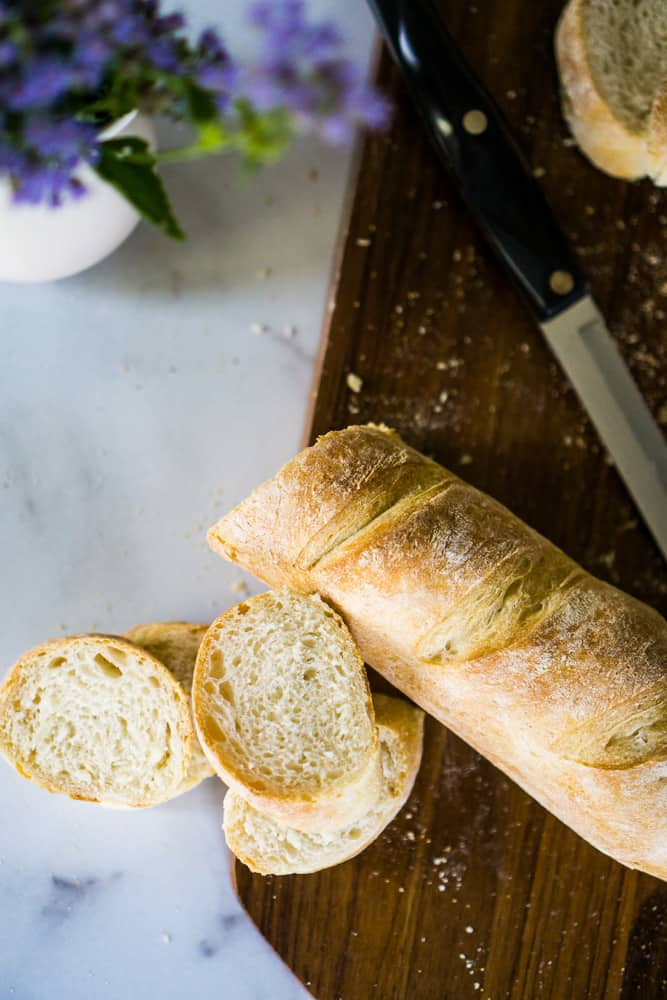sourdough baguettes on wooden cutting board with purple flowers on counter