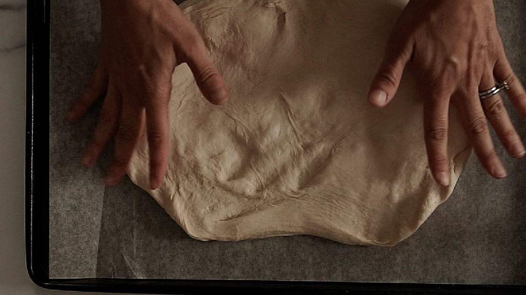 bread dough stretched out into enough oval on top of parchment paper, hands hovering over