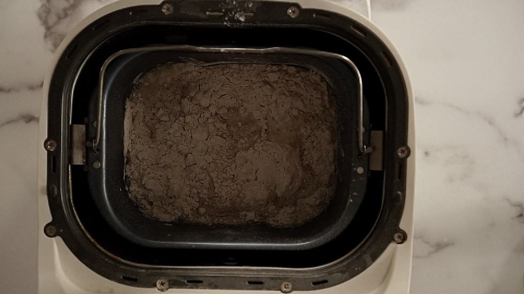 flour, yeast, and water in bread machine, unmixed