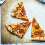 three slices of New York style pizza on parchment paper
