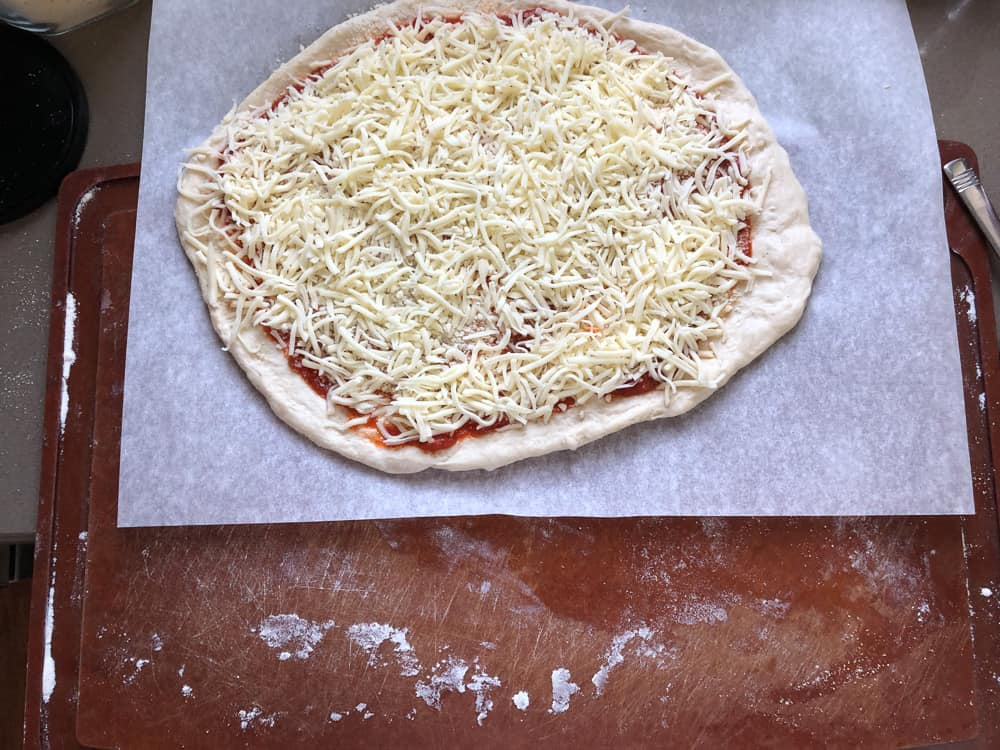 cutting board being slid under pizza and parchment paper