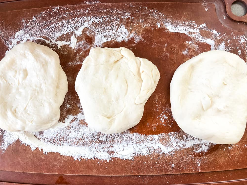 three balls of pizza dough on wooden cutting board, dusted with flour