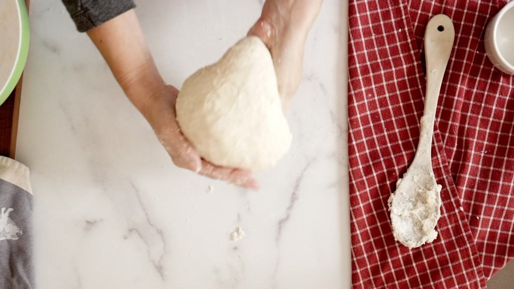 smooth sourdough pizza dough being picked up, next to wooden spoon and red tea towel