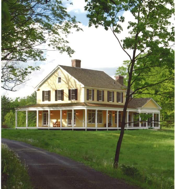 yellow farmhouse in old fashioned New England style on hill