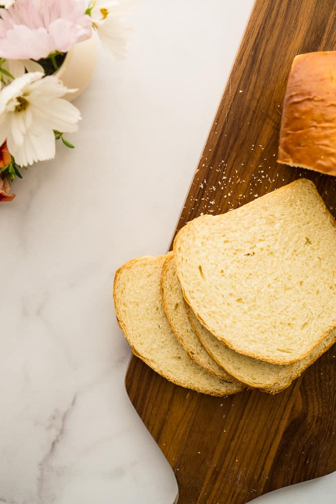 loaf of sweet hawaiian sandwich bread with four slices stacked on cutting board and white and color flowers in upper corner