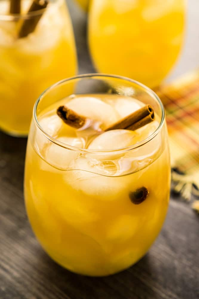 apple pear sangria in wineglass with ice and cinnamon stick. two glasses in background on wooden surface