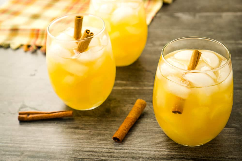 three glasses of sangria with cinnamon sticks on wooden surface- fall plaid tablecloth in background