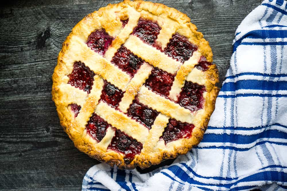 blackberry raspberry pie with lattice top on wooden surface next to blue and white plaid tea towel