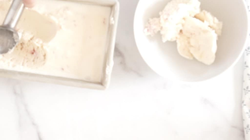 homemade candy cane ice cream being scooped out of container