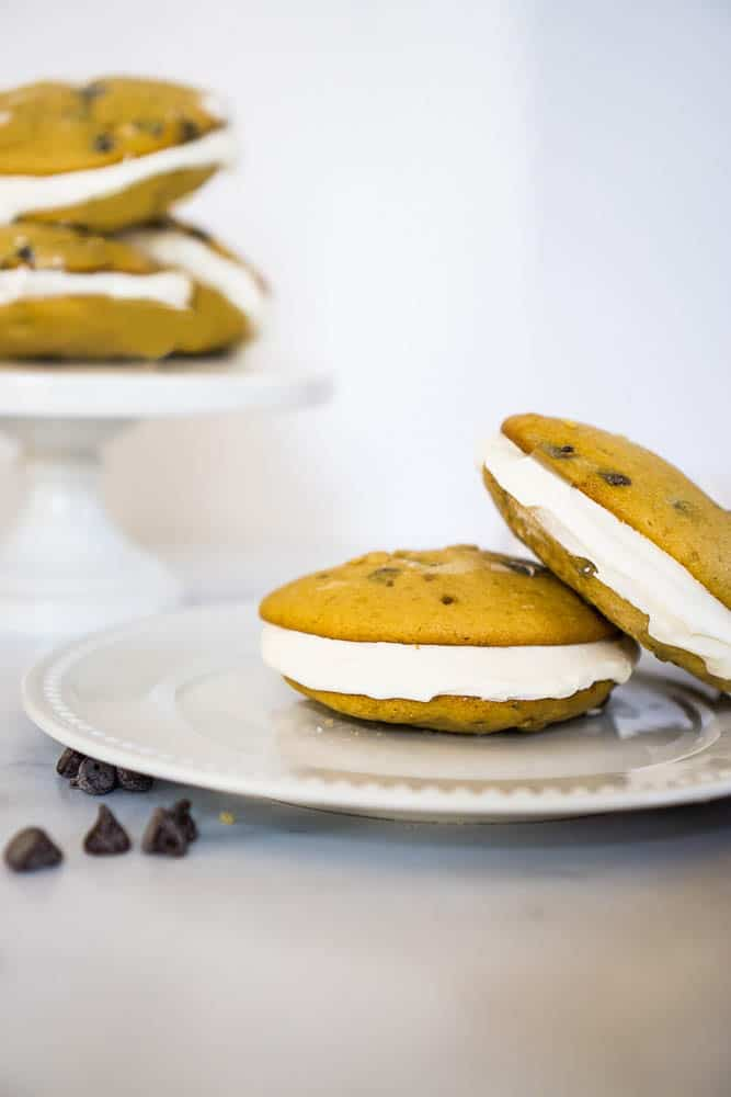 two chocolate chip whoopie pies on white white plate, three more in cake stand in background
