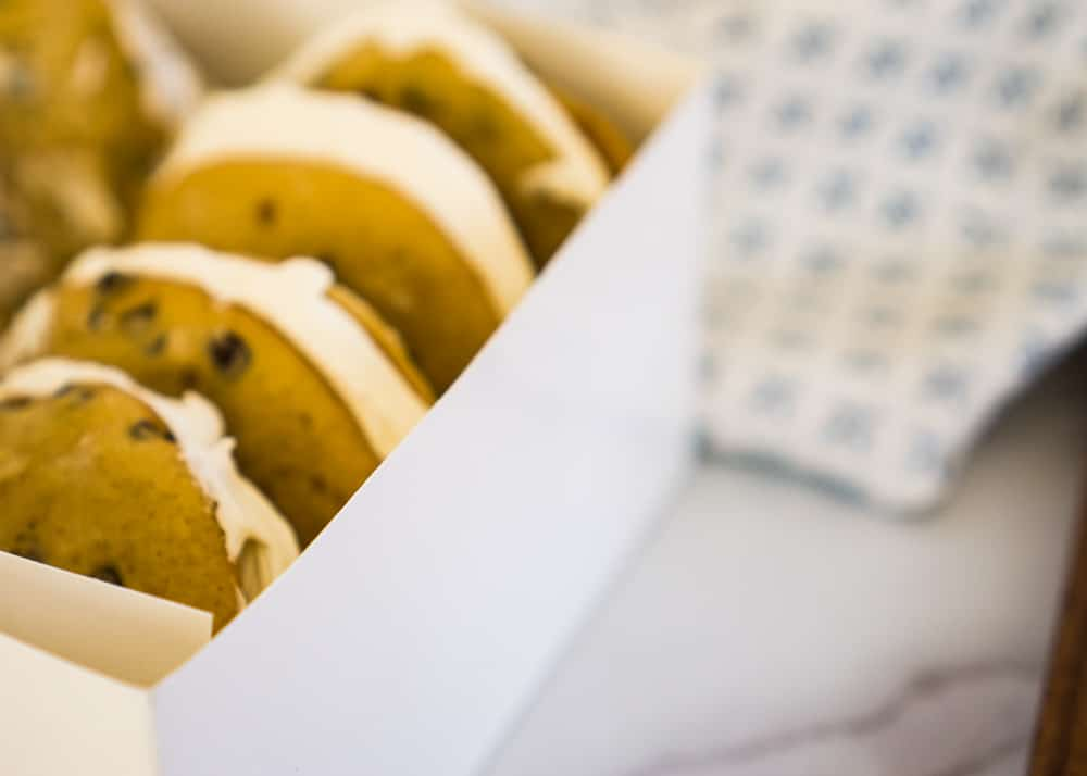 four chocolate chip Whoopie Pies in white box on marble counter