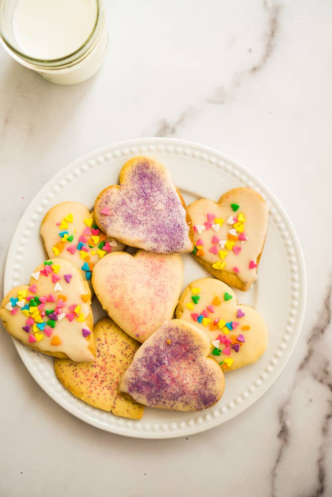 7 cut out heart shaped sugar cookies topped with glaze and purple and pink sprinkles on white plate sitting on white marble counter