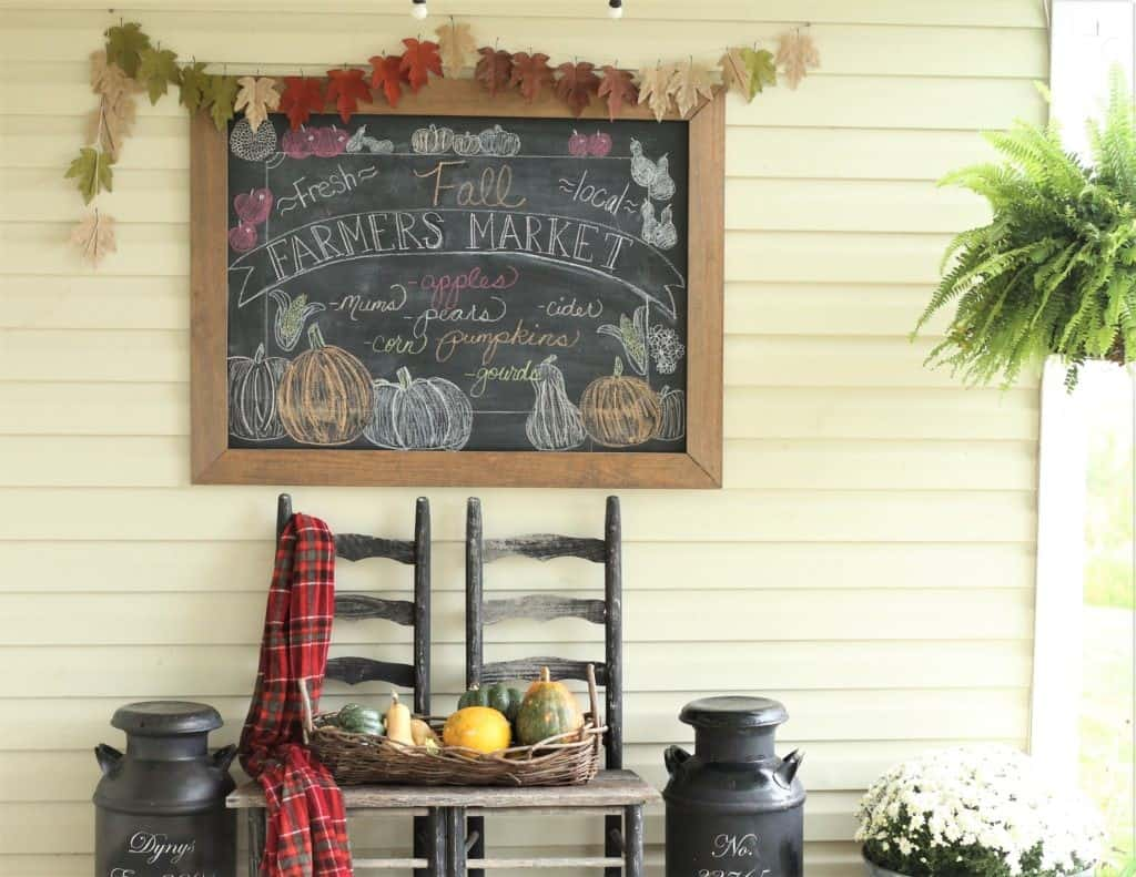 porch with two chairs and chalkboard with leaf garland
