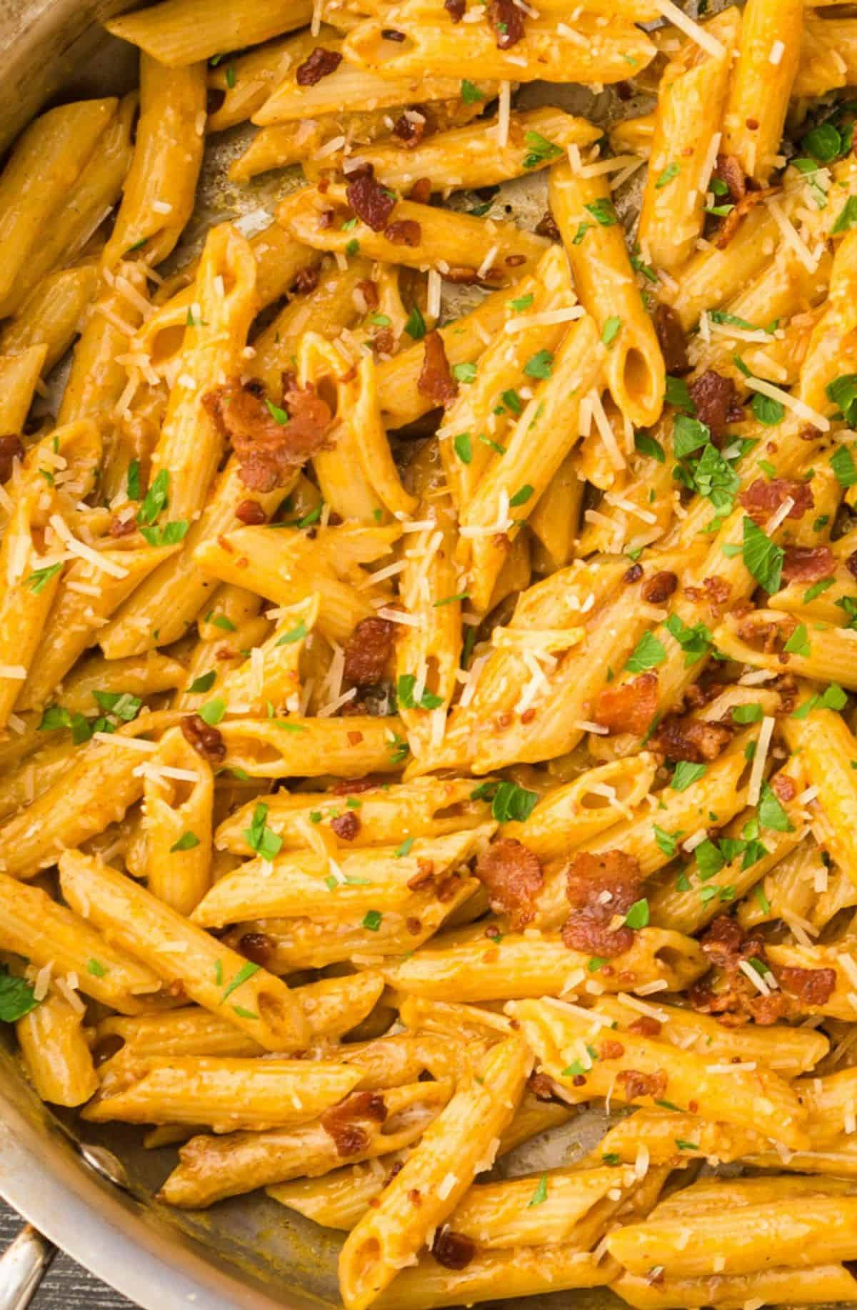 pan of penne pasta with bacon and cream sauce