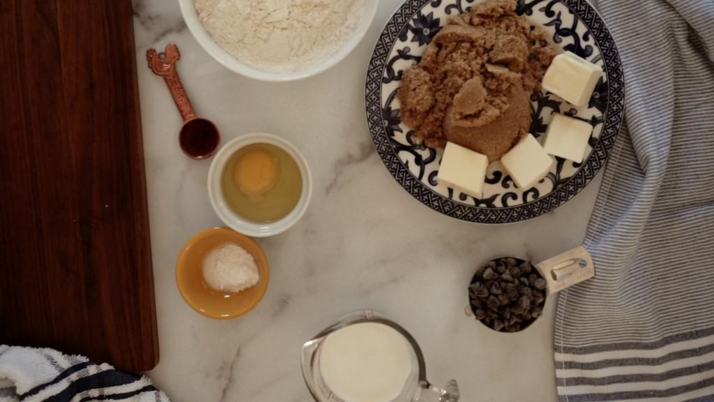 marble counter with ingredients for chocolate chip Whoopie Pies: brown sugar and butter on plate, other ingredients in measuring cups