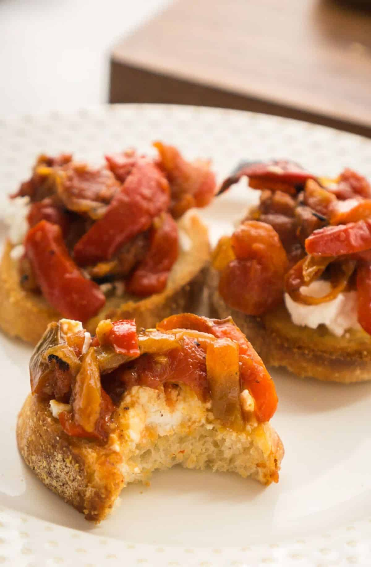 3 round toasts with goat cheese and roasted peppers