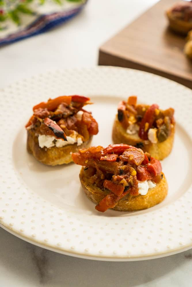 three bruschetta toasts with layer of goat cheese and red pepper topping on white plate with wooden board in background
