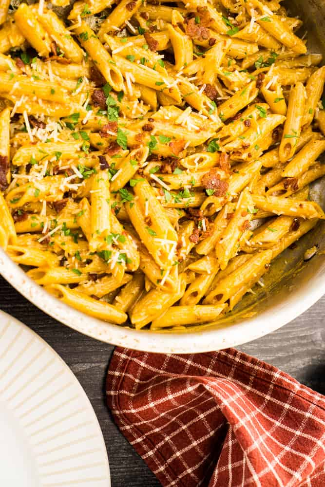 sauté pan with penne pasta covered in smoky pasta sauce, sprinkled with bacon, parmesan and parsley