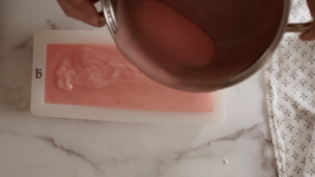 pink batter for cold process soap being poured into white silicone mold