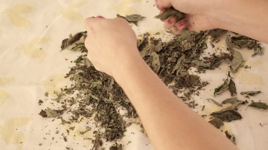 basil leaves being crumbled by hand onto yellow towel