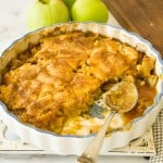 caramel apple cobbler with 1/4 missing, on marble surface with green apples in corner
