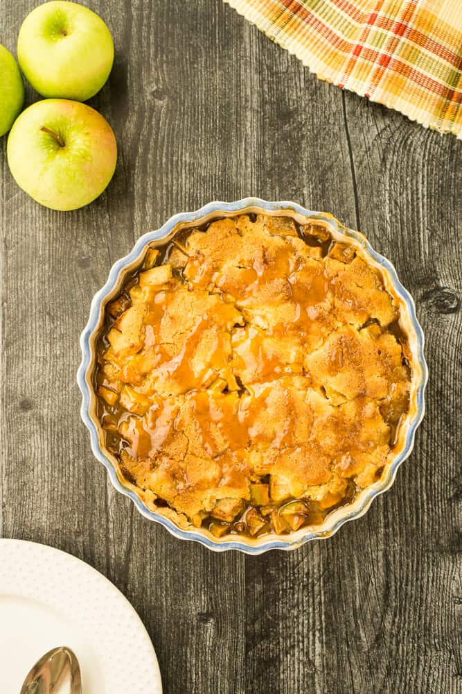 caramel apple cobbler on dark wood surface with Granny Smith apples in corner, plaid fall placemat in other corner